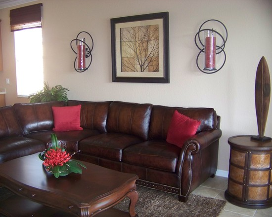 traditional brown leather sofa with red pillows unique wall lamp and